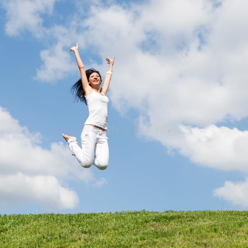 Милая женщина скача на зеленую траву стоковые фотографии rf