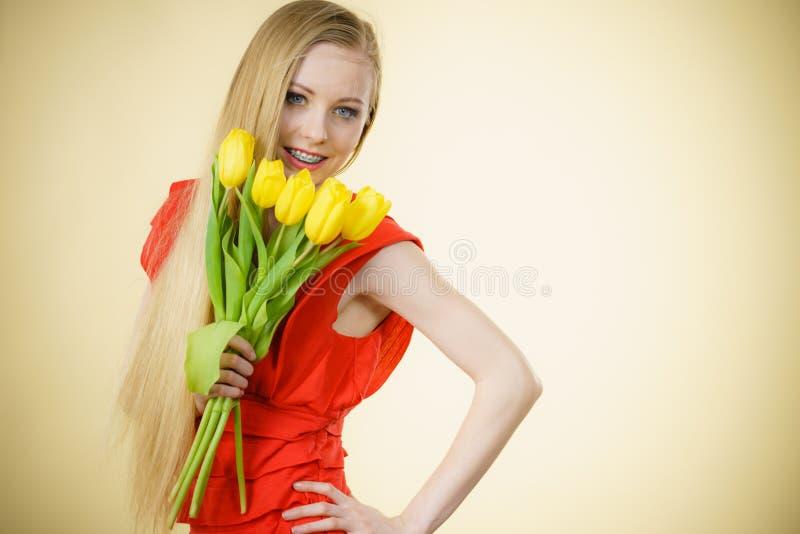 Милая женщина с желтым пуком тюльпанов стоковая фотография rf