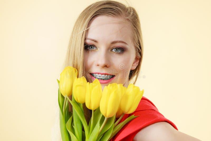 Милая женщина с желтым пуком тюльпанов стоковое изображение