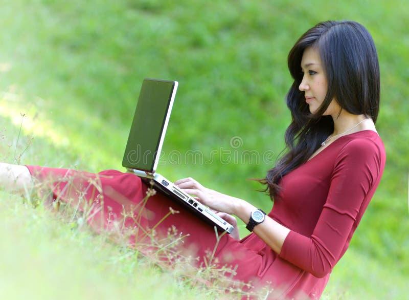 Милая женщина с компьтер-книжкой на зеленой траве на ga стоковое фото