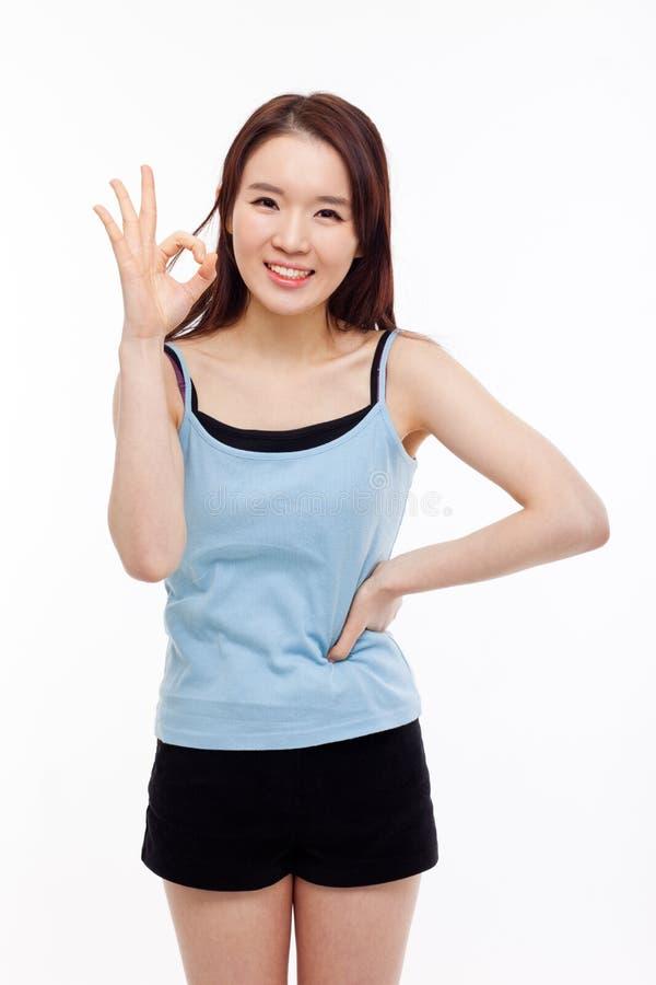 Милая женщина с одобренным жестом руки стоковые изображения