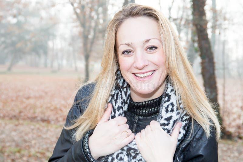 Милая женщина с шарфом в женщинах холодного дня усмехаясь стоковое изображение