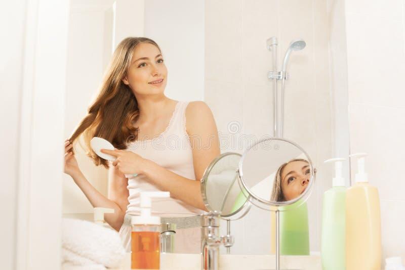 Милая женщина чистя ее длинные волосы щеткой в ванной комнате стоковое изображение rf
