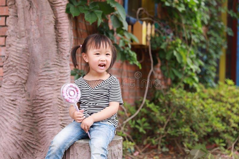 Милая капризная симпатичная прелестная игра маленькой девочки с lolipop и сидит деревом имеет потеху внешнюю в улыбке парка лета  стоковая фотография rf