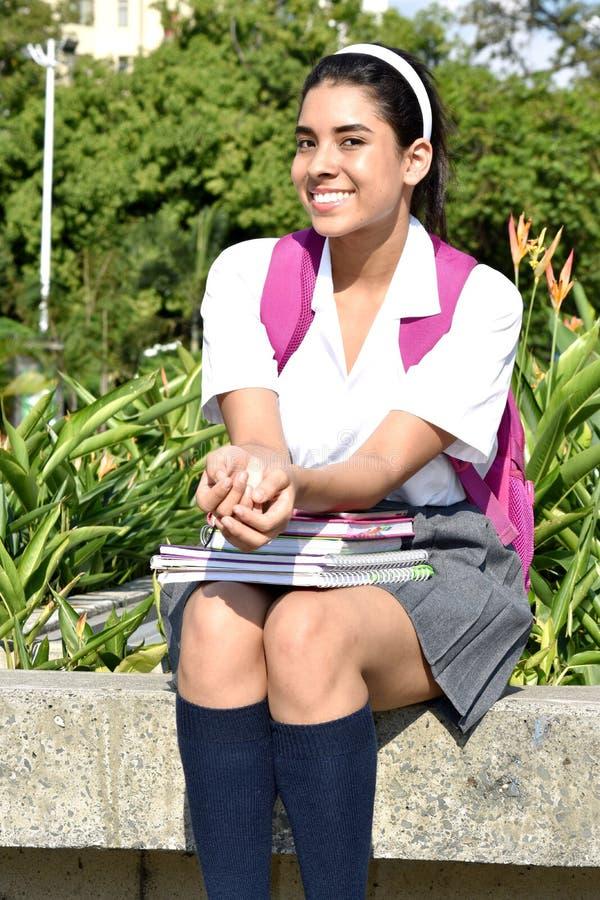 Милая колумбийская форма студента девушки усмехаясь нося с сидеть книг стоковое фото