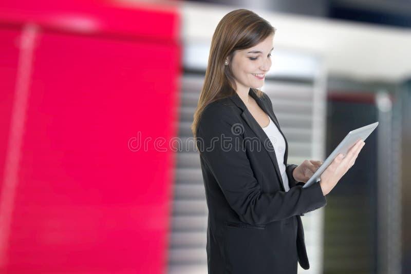 Милая коммерсантка работая с планшетом в офисе стоковая фотография