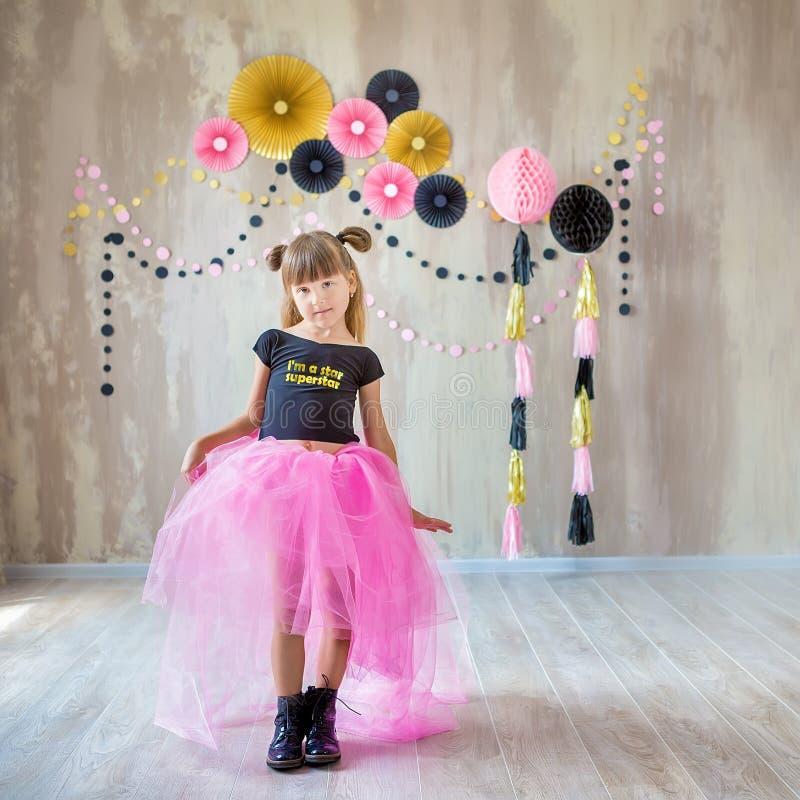 Милая красивая дама девушки представляя в причудливой фиолетовой юбке платья с 7 празднуя ее день дня рождения с потехой и радост стоковые фотографии rf