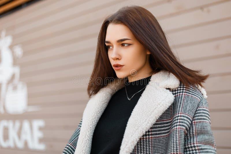Милая красивая модель молодой женщины в пальто шотландки элегантной весны сером в стойках черных ультрамодных футболки стоковые изображения rf