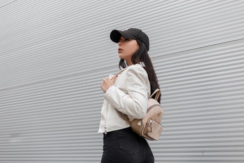 Милая красивая молодая женщина в модной белой кожаной куртке в стильных черных джинсах с прогулками ультрамодными рюкзака золота стоковое фото