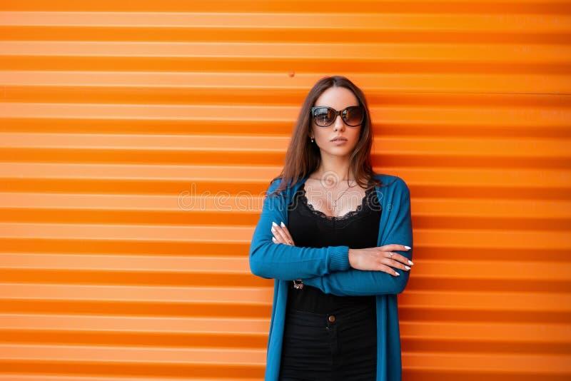 Милая красивая молодая женщина хипстера в солнечных очках в черной футболке в связанной накидке лета в винтажных джинсах стоит стоковое изображение