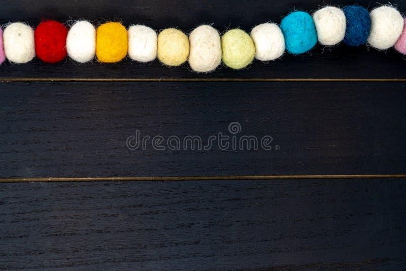 Милая красочная гирлянда ткани pom pom радуги над черным деревянным фоном стоковое фото