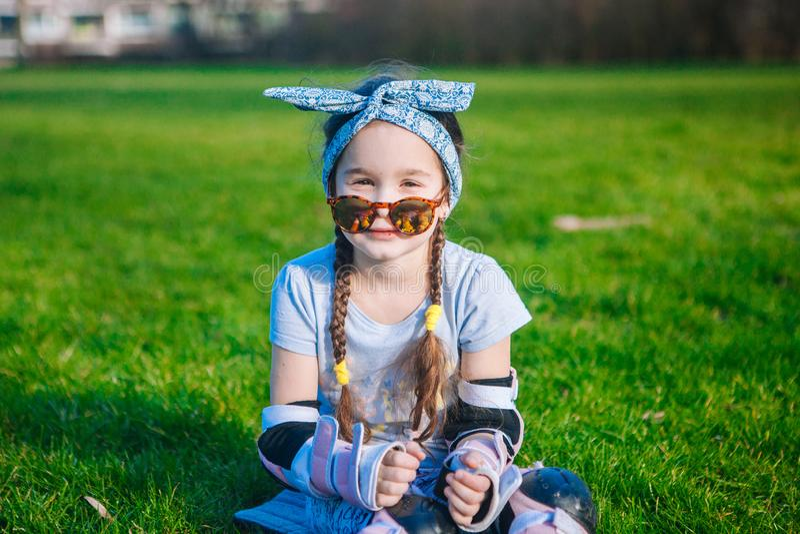 Милая курчавая девушка без зуба молока наслаждается сидеть на траве в коньках ролика и солнечных очках стоковая фотография
