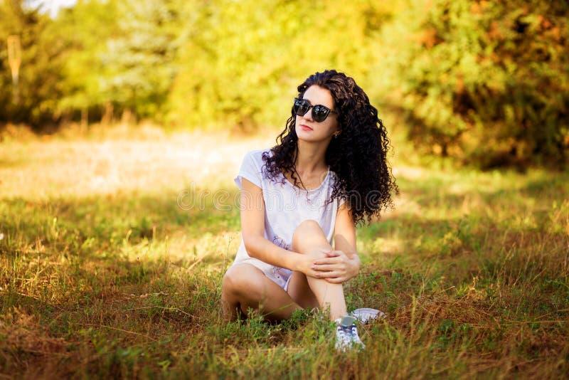 Милая курчавая женщина представляя на траве в солнечном стоковое фото rf