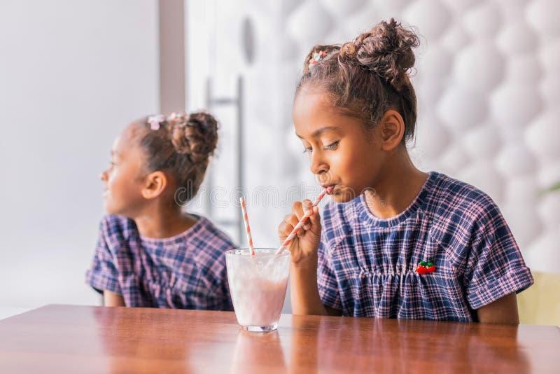 Милая курчавая темн-с волосами девушка sipping ее коктейль молока на славных выходных стоковое изображение rf