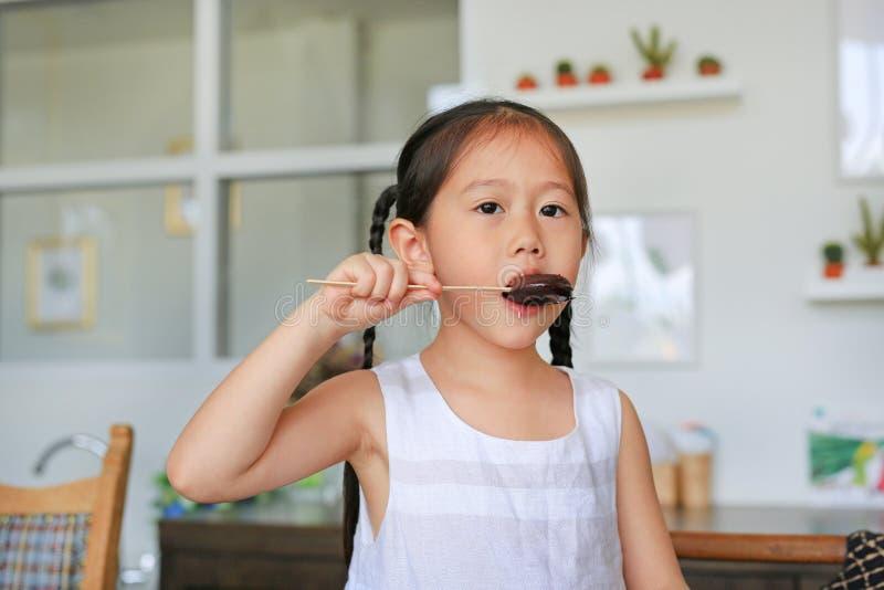 Милая маленькая азиатская девушка есть донут шоколада в кухне стоковые изображения