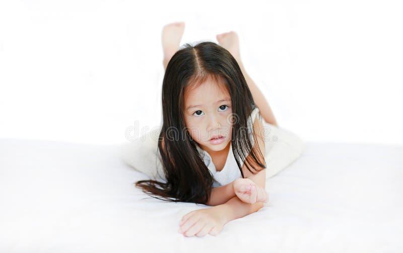 Милая маленькая азиатская девушка лежа на кровати со смотреть камеру над белой предпосылкой стоковые фотографии rf