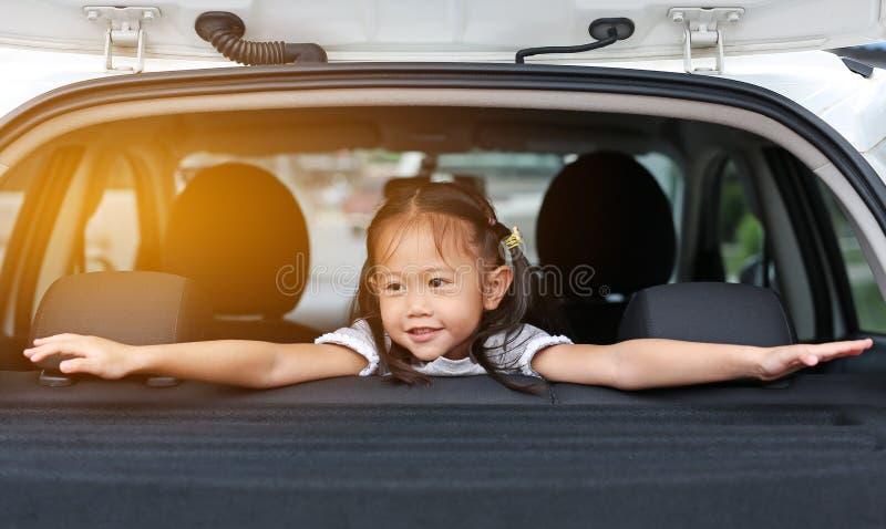 Милая маленькая азиатская девушка смотря камеру из окна автомобиля с лучами солнечного света стоковое фото