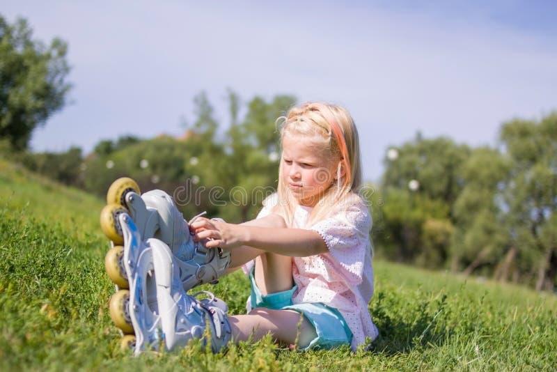 Милая маленькая белокурая девушка сидя на зеленой траве и кладя на коньки ролика - отдых, детство, концепцию на открытом воздухе  стоковое фото