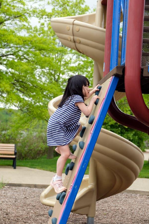 Милая маленькая девочка взбирается вверх на лестнице в спортивной площадке стоковое изображение rf