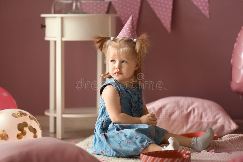 Милая маленькая девочка в комнате украшенной для дня рождения стоковое фото rf
