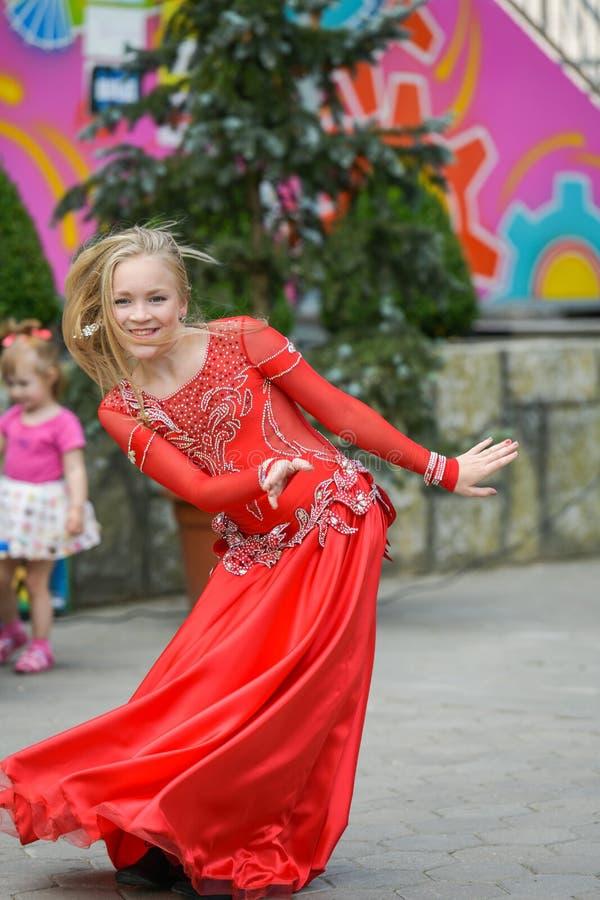 Милая маленькая девочка в красном костюме танцует на улице r Ребенок учит танец Танец шоу к стоковое фото