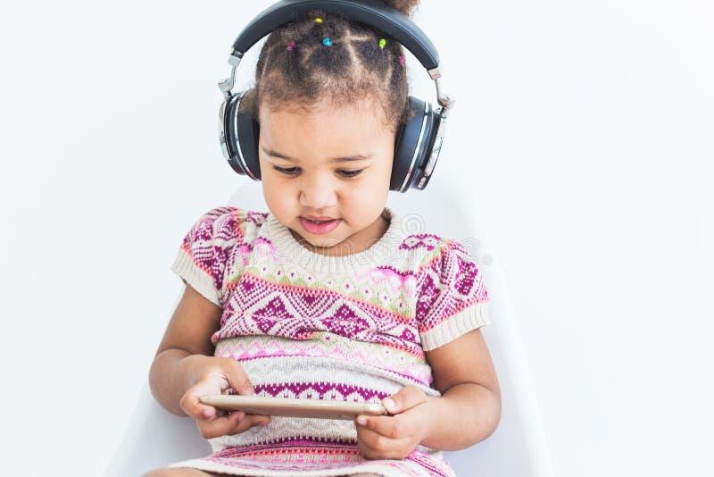 Милая маленькая девочка в пестротканом платье, слушает музыку с наушниками и использует смартфон на белой предпосылке стоковые изображения