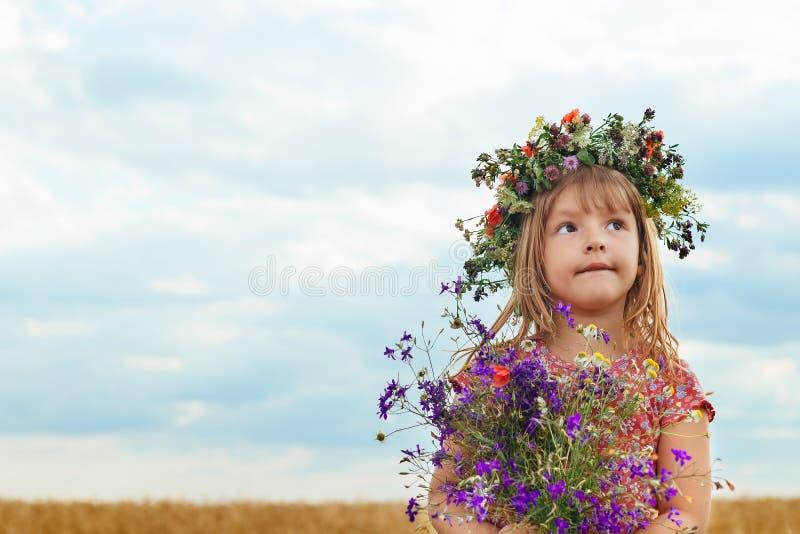 Милая маленькая девочка в пшеничном поле лета стоковое фото rf