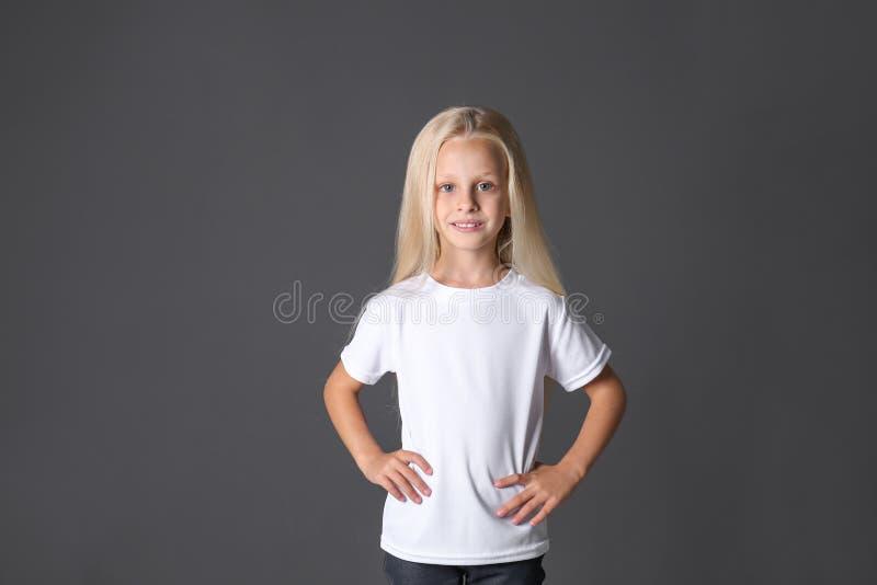 Милая маленькая девочка в футболке на темной предпосылке стоковые фотографии rf