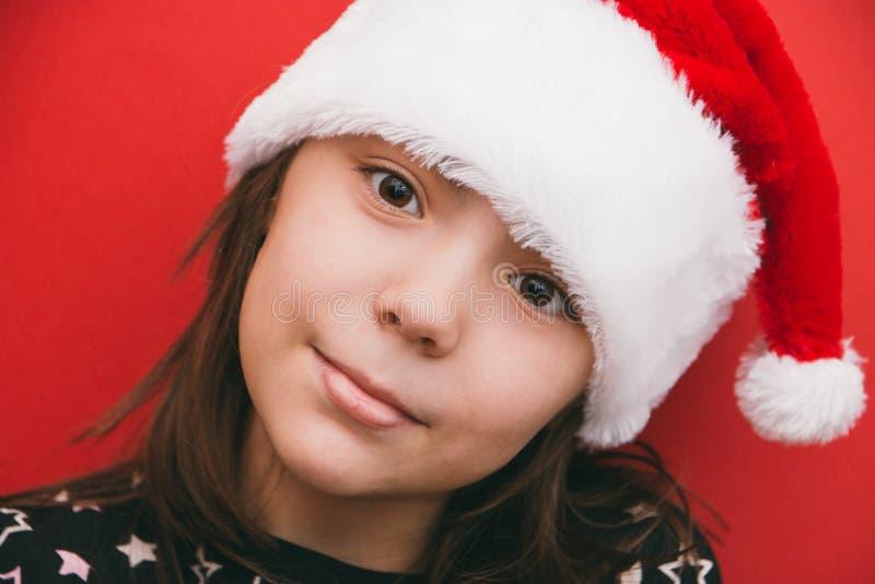 Милая маленькая девочка в шляпе Санта Клауса на красной предпосылке стоковое изображение rf