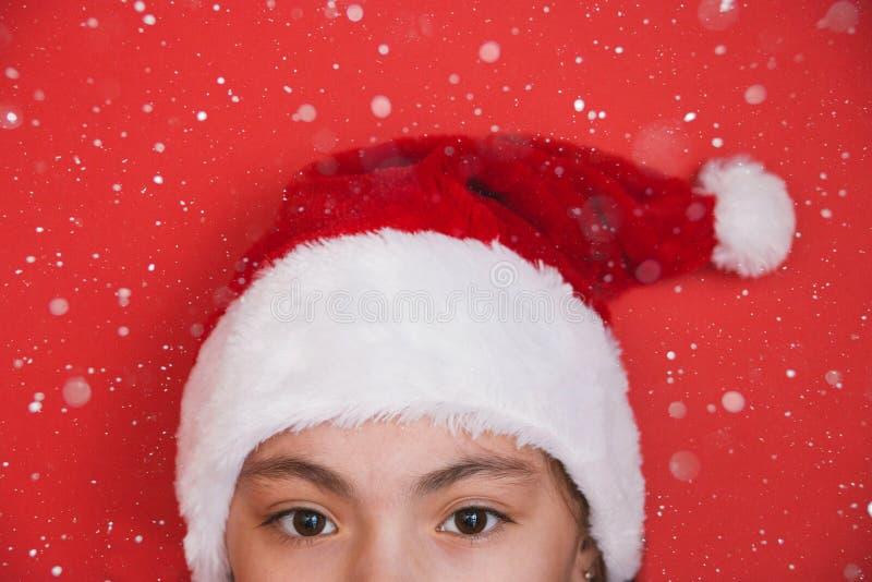 Милая маленькая девочка в шляпе Санта Клауса на красной предпосылке стоковое фото