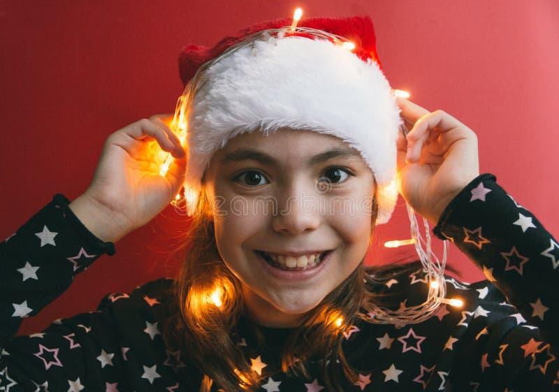 Милая маленькая девочка в шляпе Санта Клауса с гирляндой на красной предпосылке стоковые фото