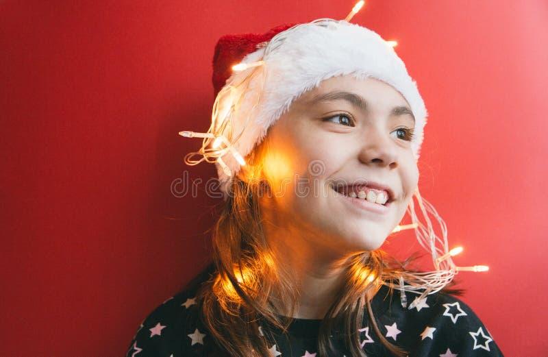 Милая маленькая девочка в шляпе Санта Клауса с гирляндой на красной предпосылке стоковые изображения