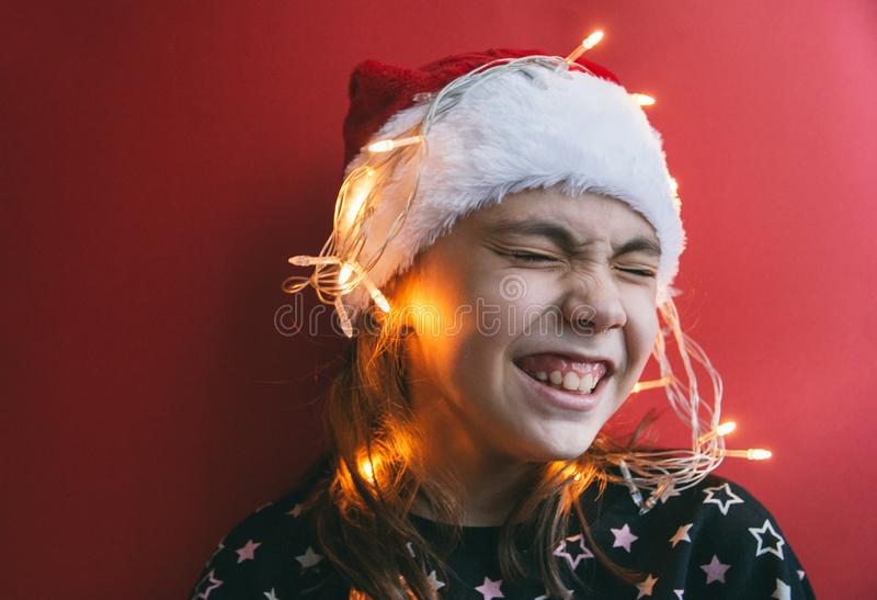 Милая маленькая девочка в шляпе Санта Клауса с гирляндой на красной предпосылке стоковое фото rf