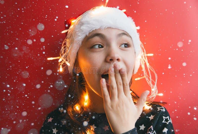 Милая маленькая девочка в шляпе Санта Клауса с гирляндой на красной предпосылке стоковая фотография rf