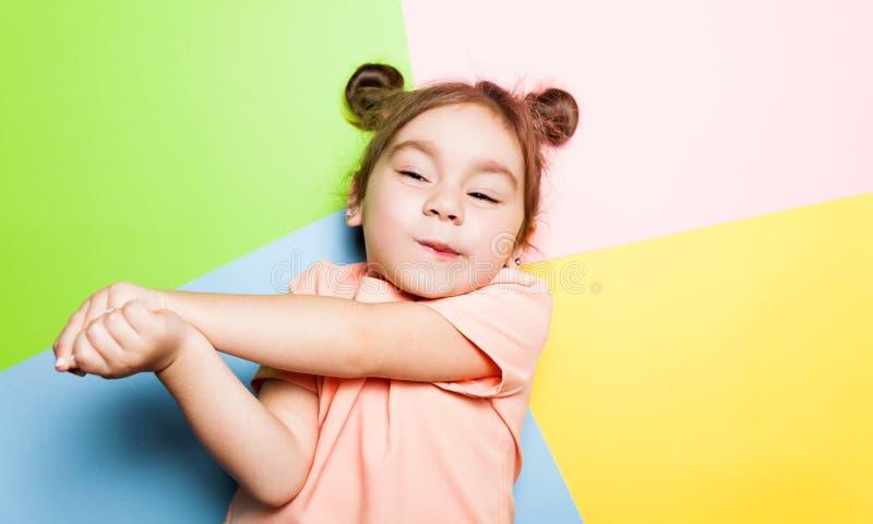 Милая маленькая девочка 4 год с смешной стороной на multicolor предпосылке Яркие цвета и стильное изображение стоковое фото rf