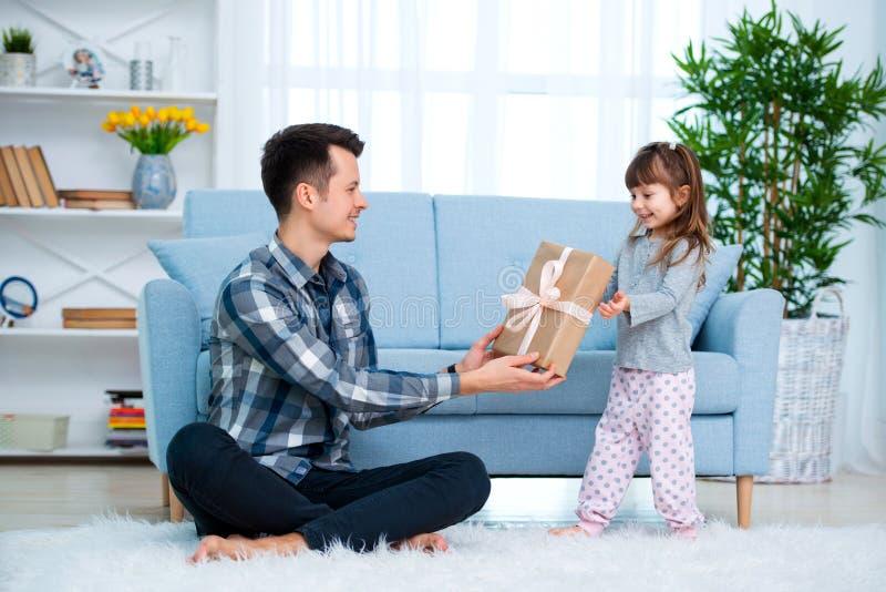 Милая маленькая девочка, дочь, сестра дает подарочную коробку молодым отцу или брату папы Оба усмехаются Concep праздника Дня отц стоковые фото