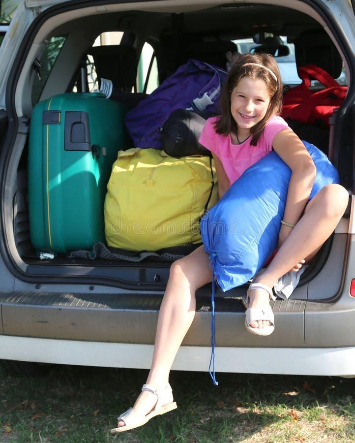 Милая маленькая девочка заполняет чемоданы на автомобиле стоковое фото