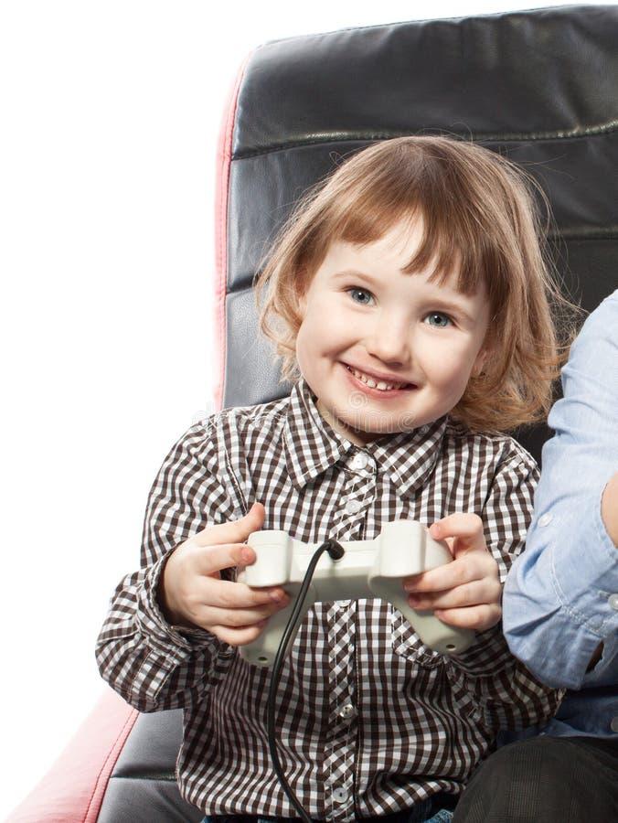 Милая маленькая девочка играя видеоигру стоковое изображение