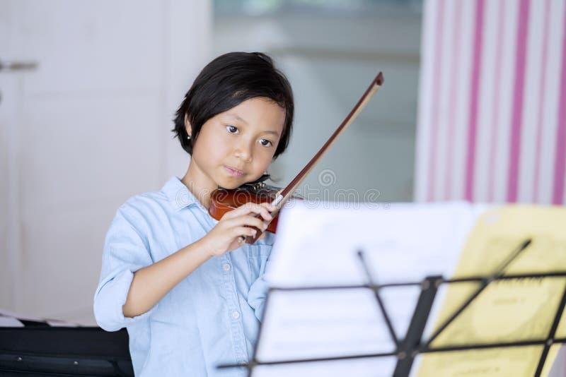 Милая маленькая девочка играя скрипку стоковые изображения rf