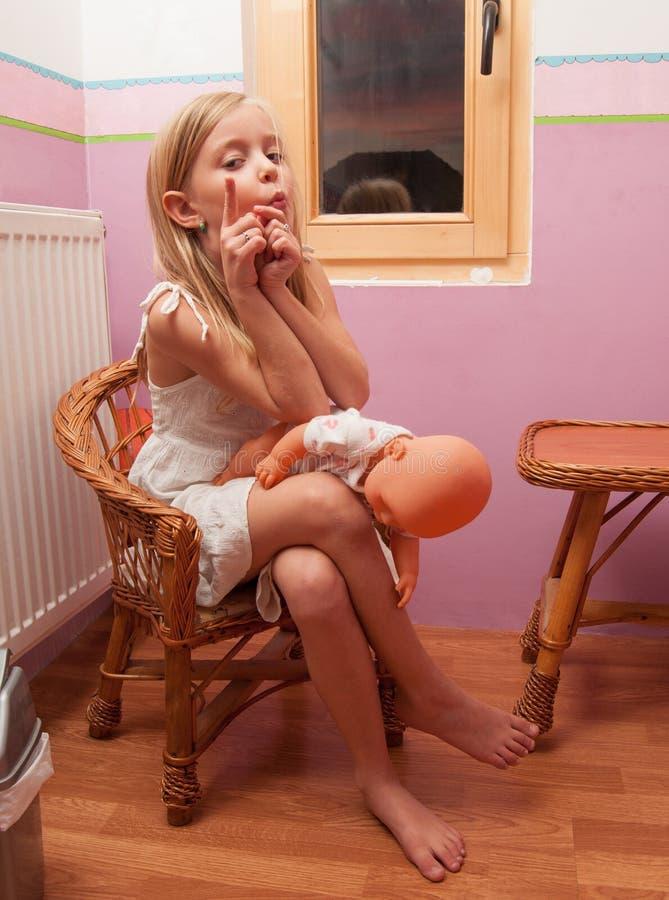 Милая маленькая девочка играя с игрушкой младенца в ее комнате стоковые изображения rf