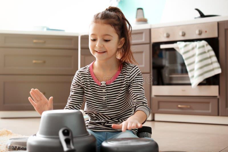 Милая маленькая девочка играя с kitchenware как барабанчики стоковое изображение rf