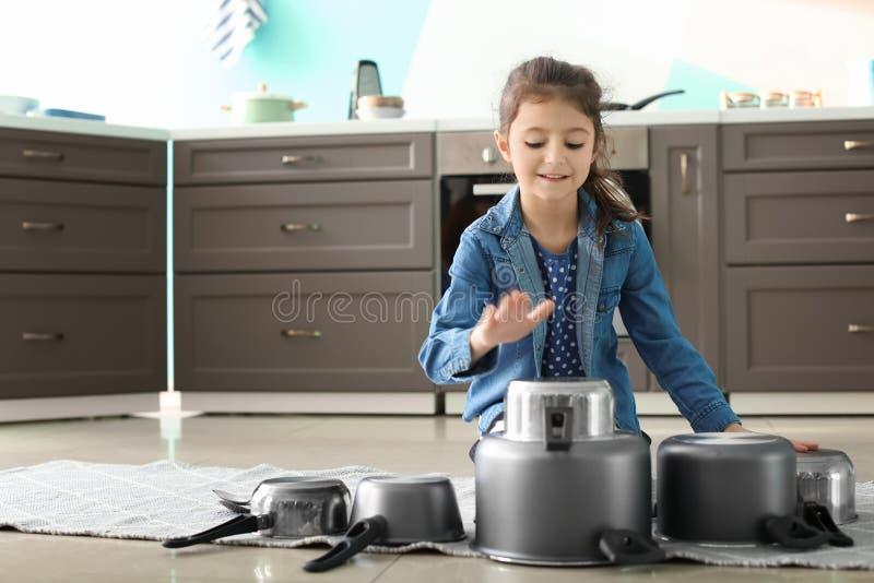 Милая маленькая девочка играя с kitchenware как барабанчики стоковая фотография