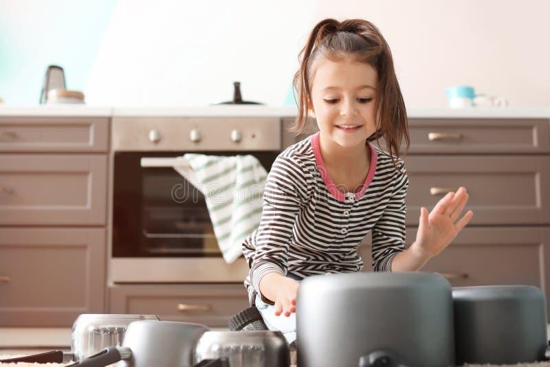 Милая маленькая девочка играя с kitchenware как барабанчики стоковые изображения rf
