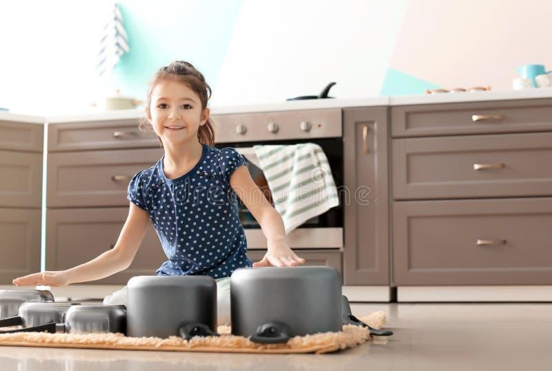 Милая маленькая девочка играя с kitchenware как барабанчики стоковые фото