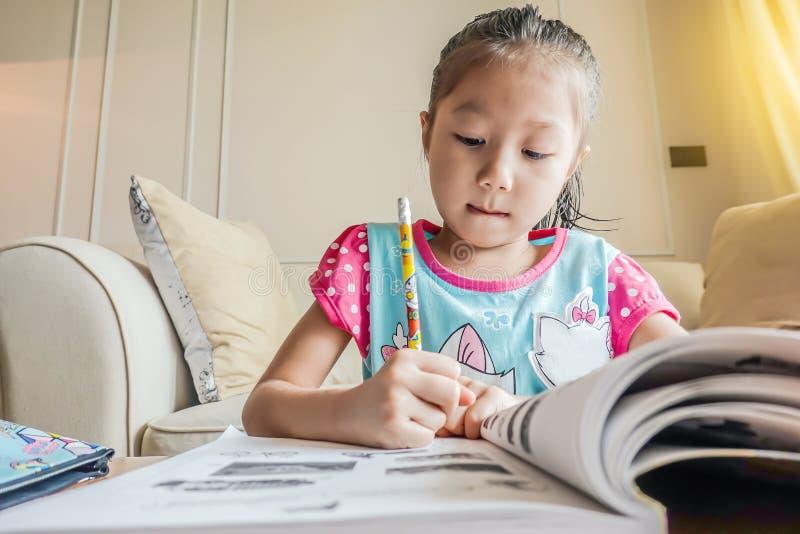 Милая маленькая девочка и удержание карандаша и запись на книге для того чтобы сделать домашнюю работу стоковое изображение