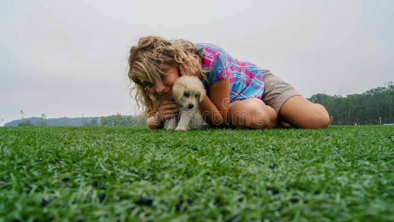 Милая маленькая девочка лежа на траве с ее щенком labrador 3 месяцев старым стоковое изображение
