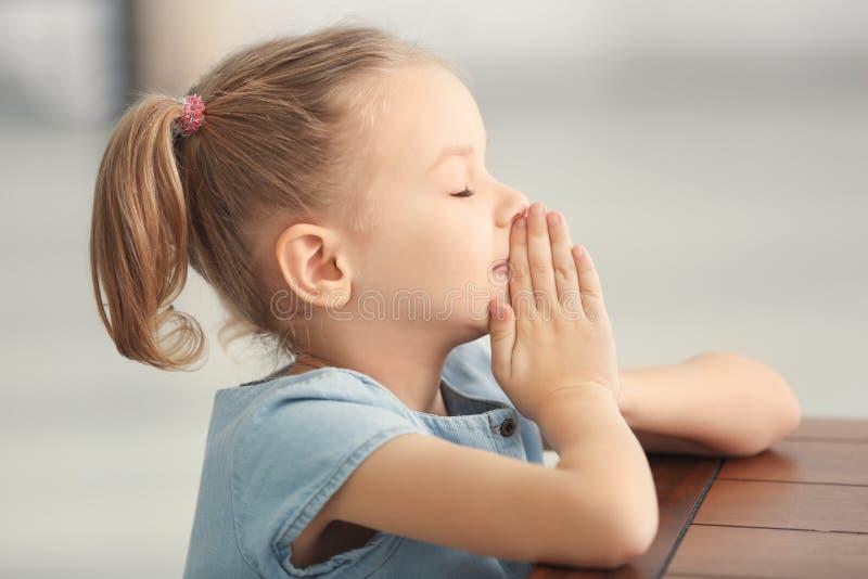 Милая маленькая девочка моля дома стоковая фотография