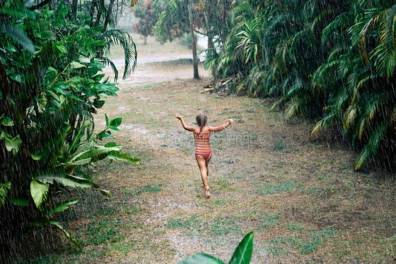 Милая маленькая девочка наслаждается дождем и танцами на улице летом стоковые фотографии rf