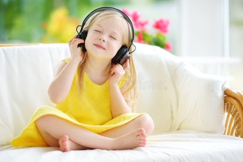 Милая маленькая девочка нося огромные беспроволочные наушники Милый ребенок слушая к музыке Школьница имея потеху слушая к ` s ре стоковая фотография
