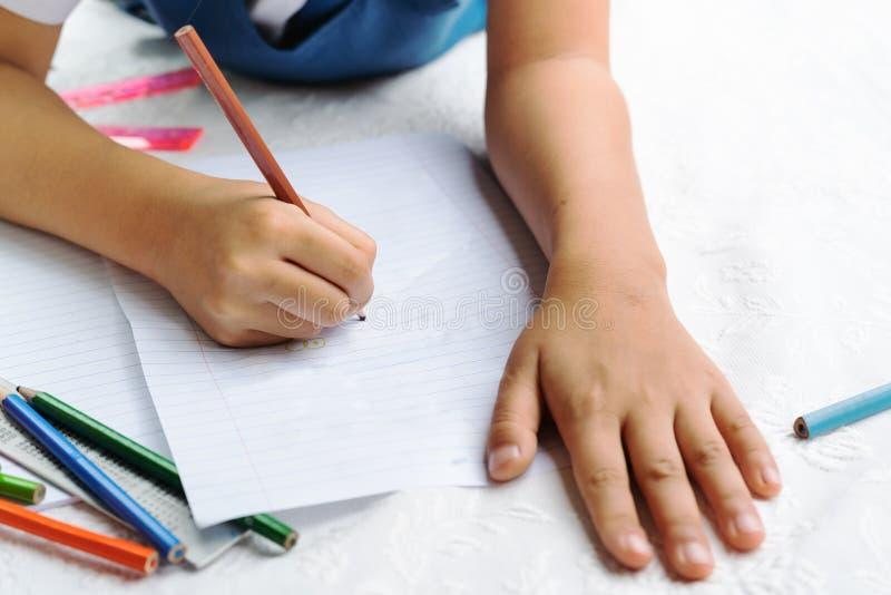 Милая маленькая девочка пишет к сочинительств-книгам Решение уроков девушка положенная вниз с рисовать изображение стоковые изображения rf